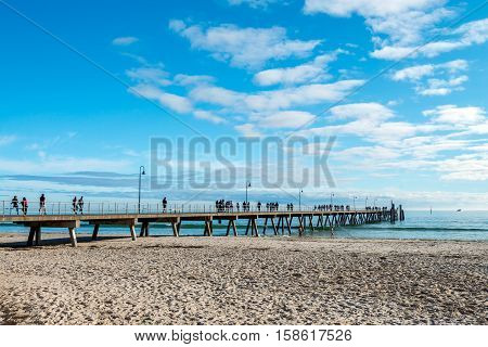 Adelaide Australia - August 16 2015: People walking along Glenelg Beach jetty on a warm summper day
