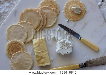 Crisp savoury biscuits and cheese on a board.