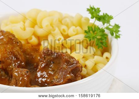 bowl of fresh beef goulash with cooked rigatoni pasta - close up