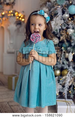 little girl three years in a blue dress licks a great round colorful candy