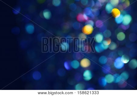 Colorful beautiful blurred bokeh background with copy space. Holiday texture. Glitter multicolored light spots on navy blue backdrop defocused