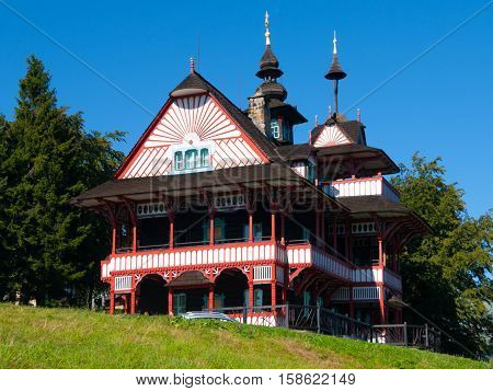 Picturesque timbered mountain cottage Mamenka in slavic folk secession architectural style on sunny summer day, Pustevny, Beskids, aka Beskydy Mountains, Moravia, Czech Republic.