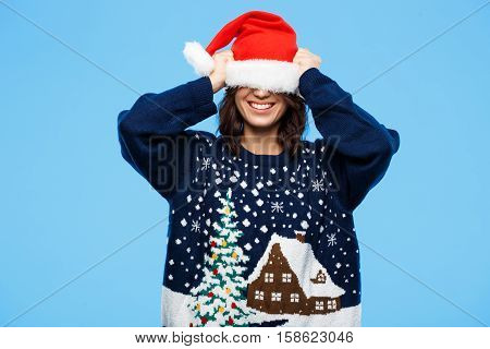 Young beautiful brunette girl in knited sweater and christmas hat smiling  over blue background. Copy space.