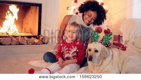 Family Christmas celebration next to fireplace