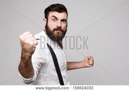 Angry rude young handsome man in suit with suspenders showing fist over white background. Copy space.