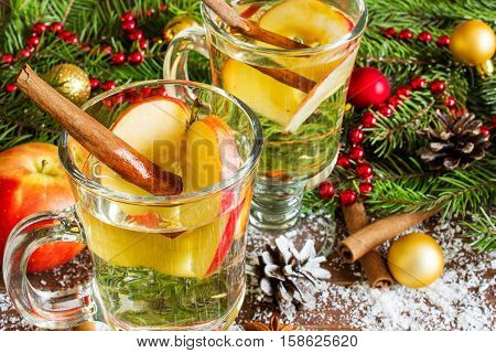 two glasses of hot mulled cider with spices and sliced apple on wooden background. close up
