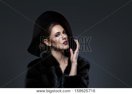 Beautiful young woman with glamorous make-up in luxurious fur coat on naked body and fashion hat on black background. Copy space.
