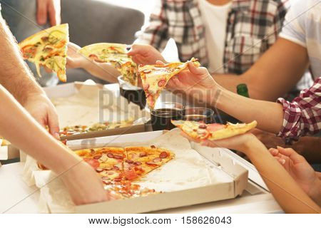 Friends eating pizza at home party, closeup
