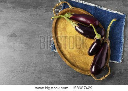 Fresh aubergines on tray