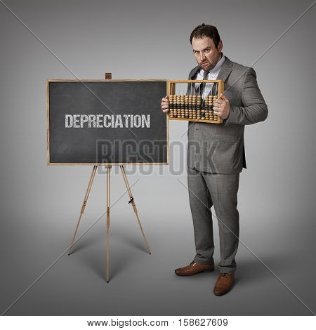 Depreciation text on blackboard with businessman and abacus