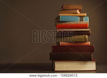 Pile of books on table and dark background