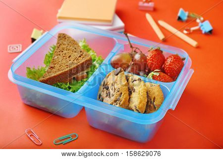 Tasty sandwich and fruits in lunchbox and stationery on red background