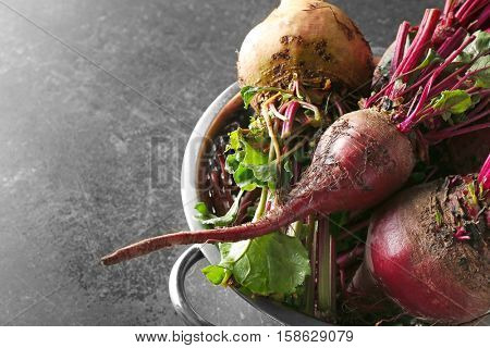 Young beets in strainer on grey background