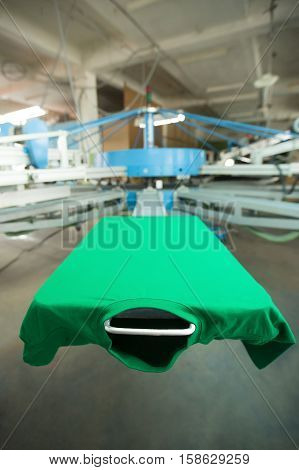 Green t-shirt silk screen printing machine, look of the mock up clothing before high quality printing process. Vertical image