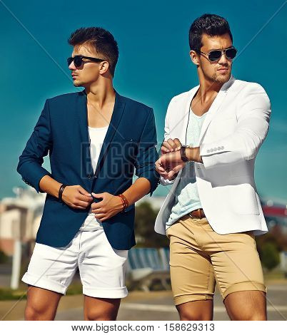 Fashion portrait of two young sexy handsome men models in casual cloth suit in sunglasses in the street behind blue sky