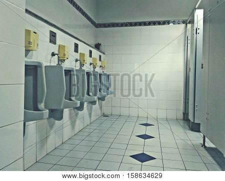 The Men restroom and white urinals in retro color mode.