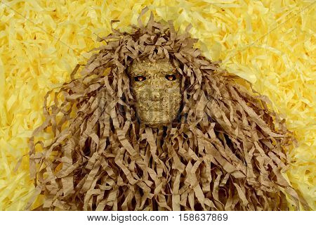 Man in a mask made of paper with fire in his eyes. On a bright yellow background with paper strips