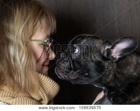 The girl and funny dog nose to nose. The concept of a pet dog with attitude communication