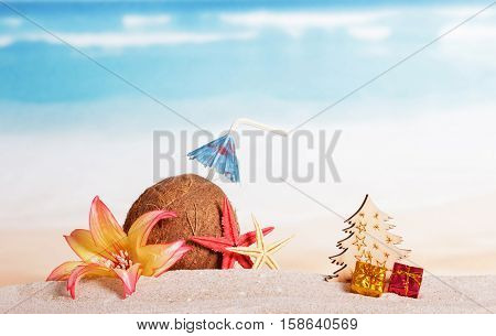 Christmas accessories in the sand, coconut, tree, presents on background of ocean