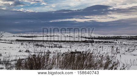 Evening winter landscape, a passenger train, the beautiful sky, the steppe, severe landscape, grunge landscape