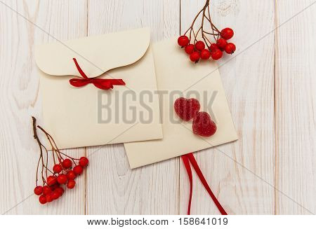 Empty envelopes with red rowan and stripe.Two red hearts candy.White wooden table.Poscard with space