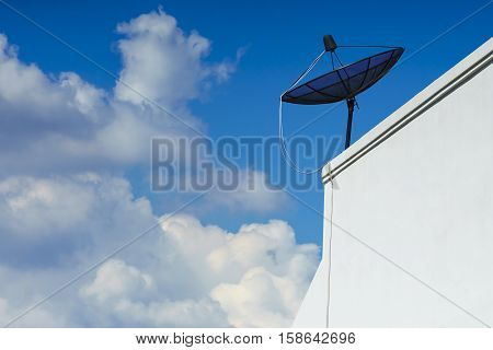 satellite dish stands on the top of a white building with a blue sky and cloudy day.