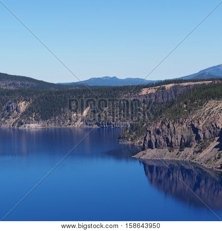 The jagged rim of Crater Lake reflects in the deep blue water on a sunny summer morning.