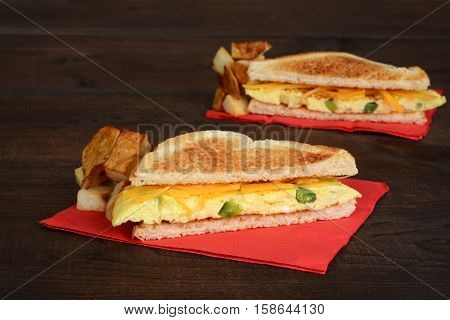closeup omelette sandwich with fries on red napkin