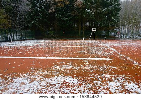Abandoned clay tennis court which is peppered the first winter snow.