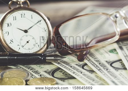 Vintage style finance concept with glasses dollar bills retro clock coins and fountain pen.