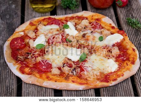 Homemade pizza with tomato sauce tomatoes cheese and mozzarella