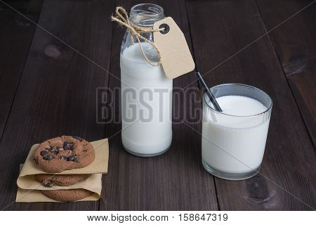 bottle of milk with carton label tag with one transparent glass, black straw and few brown cookies on dark wooden background