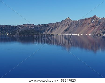 Wizard Island and reflections in Crater Lake on a sunny summer morning.