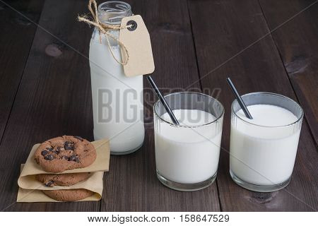 bottle of milk with carton label tag with two transparent glasses, black straw and few brown cookies on dark wooden background