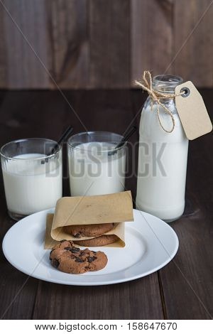 bottle of milk with carton label tag with two transparent glasses, black straw and few brown cookies on white plate on dark wooden background