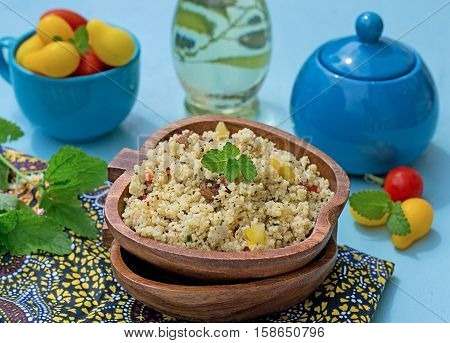 Arabian salad with couscous and vegetables tabbouleh on blue background