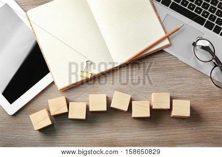 Tablet, copybook and wooden cubes on color background