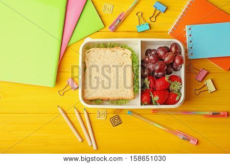Lunchbox with tasty meal and stationery on yellow wooden background