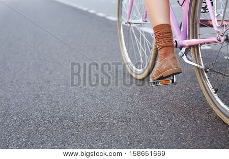 Close up view of female leg on bicycle pedal