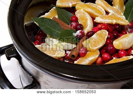 Homemade cranberry sauce ingredients of cinnamon oranges cranberries bay leaf simmering in a crock pot isolated on a white background