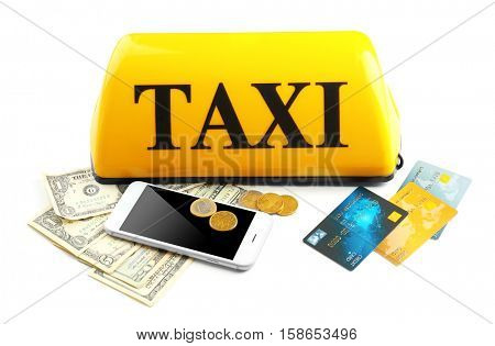 Yellow taxi roof sign with phone, money and credit cards on white background, closeup