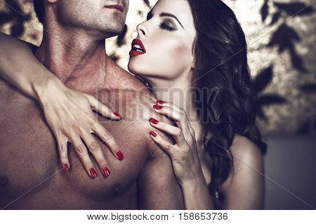 Sensual lustful woman with red lips embrace sexy man body at night lovers