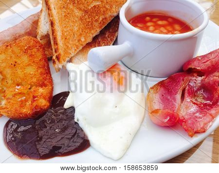 Traditional full English breakfast with fried egg, bacon, sausage, toast, hash brown and beans