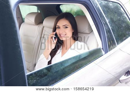 Young woman talking on phone on back seat in car