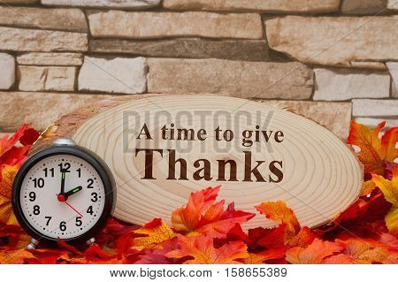 Thanksgiving message Some fall leaves an alarm clock and wood plaque on weathered brick with text A time to give Thanks