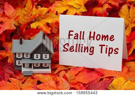 Selling your home in the fall season Some fall leaves and gray house and greeting card with text Fall Home Selling Tips