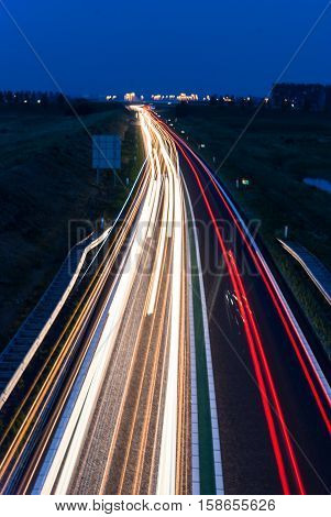 Red and white lights of cars on busy highway during the evening