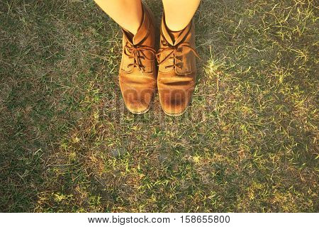 Feet in shoes on grass background