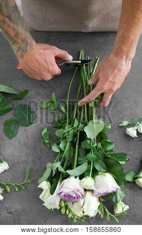 Male florist making bouquet at flower shop