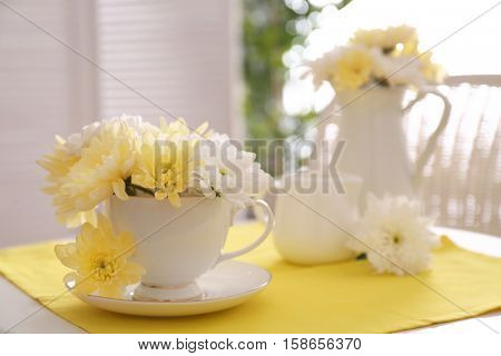 Flower bouquet of chrysanthemum in cup on yellow napkin